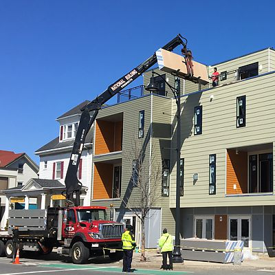 Drywall being delivered by boom truck into upper levels of building