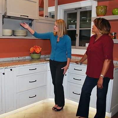Kitchen Views designer shows a customer the cabinetry features in a showroom