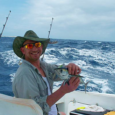 Caribbean guest smiling because he caught a fish