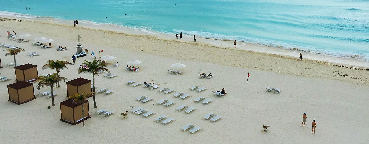 Beach with lounge chairs, cabanas and people at Le Blanc in Cancun